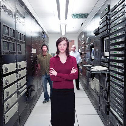 Woman standing with coworkers in server room (selective focus)