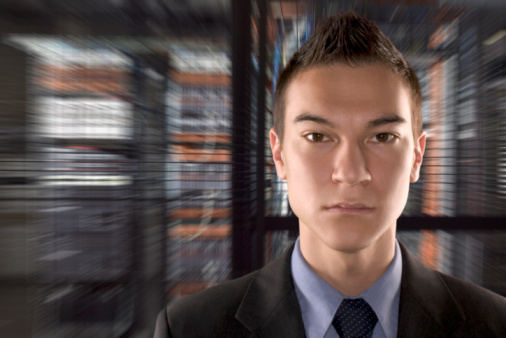 Serious Businessman in Server Room with Blurred Background