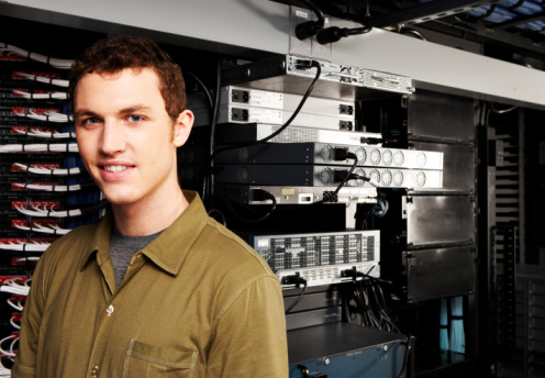 Computer Technician in Front of Equipment Racks